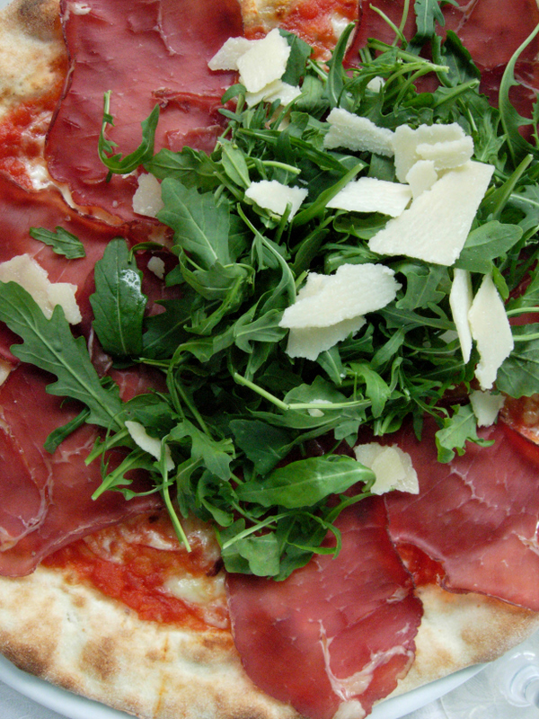 Pizza topped with bresaola and fresh rucola.  Photo by Dr. Beall-Fofana.